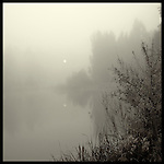 A misty view across a lake with the sun reflected in the water
