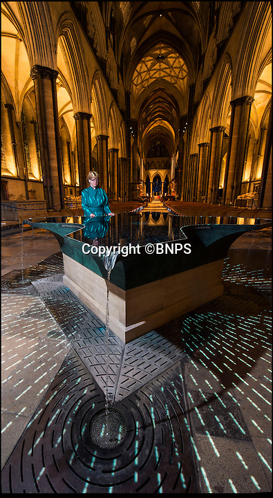 BNPS.co.uk (01202 558833)Pic: PhilYeomans/BNPS<br /> A festive 'Star of Bethlehem' art installation was switched on in Salisbury Cathedral yesterday. <br /> <br /> Artist Bruce Munro's represents the biblical star that led the three wise men to Bethlehem, and radiating lines of morse code actually quote from Matthew's gospel.<br /> <br /> Canon Treasurer of Salisbury Cathedral, Sarah Mullally views the font at dusk, the beautiful artwork will remain in the historic cathedral untill after Christmas.