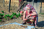 Maya Devi Adhikari, 80, dries plants in the sun in Makaising, a village in the Gorkha District of Nepal that was hard hit by a devastating 2015 earthquake.