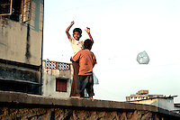 Two young boys play with a kite made from a plastic bag on 21st Oct 2006