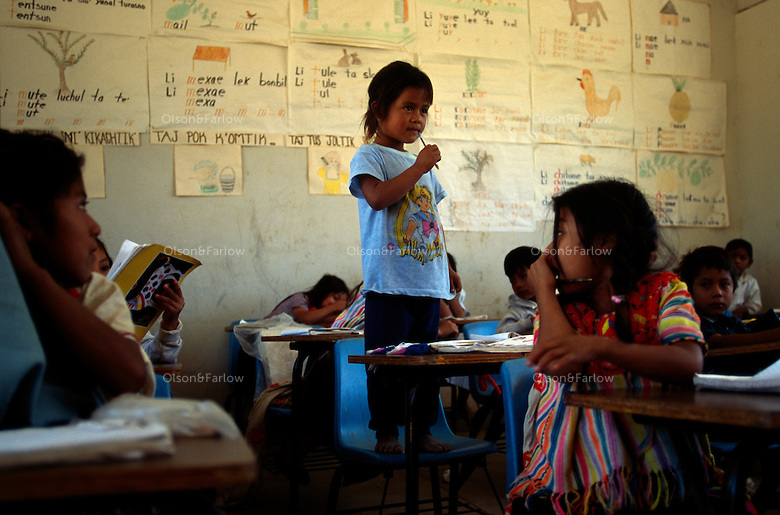Young girl stands on her chair to answer the teacher's question in a classroom of Mayan Indian children.  Children learn Spanish but also study their own local language in the schools in rural Chiapas.