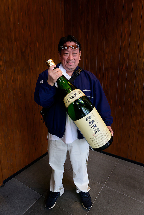 Munehiro Sata, President of Sata Souji Shoten Shochu Distillery, holding a large empty bottle of shochu. Minami Kyushu, Kagoshima Pref, Japan, December 21, 2016. The Sata Souji Shoten Shochu Distillery makes shochu spirits from local sweet potatoes. In recent years the distillery has imported grappa, brandy, calvados stills from Europe to experiment with new distilling techniques. They have attracted considerable attention from the media and other distillers as leading innovators in their industry.