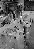 A.S.Neill, wearing flat cap, in the background, carpentry workshop, Summerhill school, Leiston, Suffolk, UK. 1968.