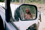 Himba woman reflected in the review mirror near Epupa falls, Namibia
