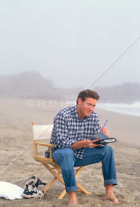 Young man sitting at the beach writing postcards