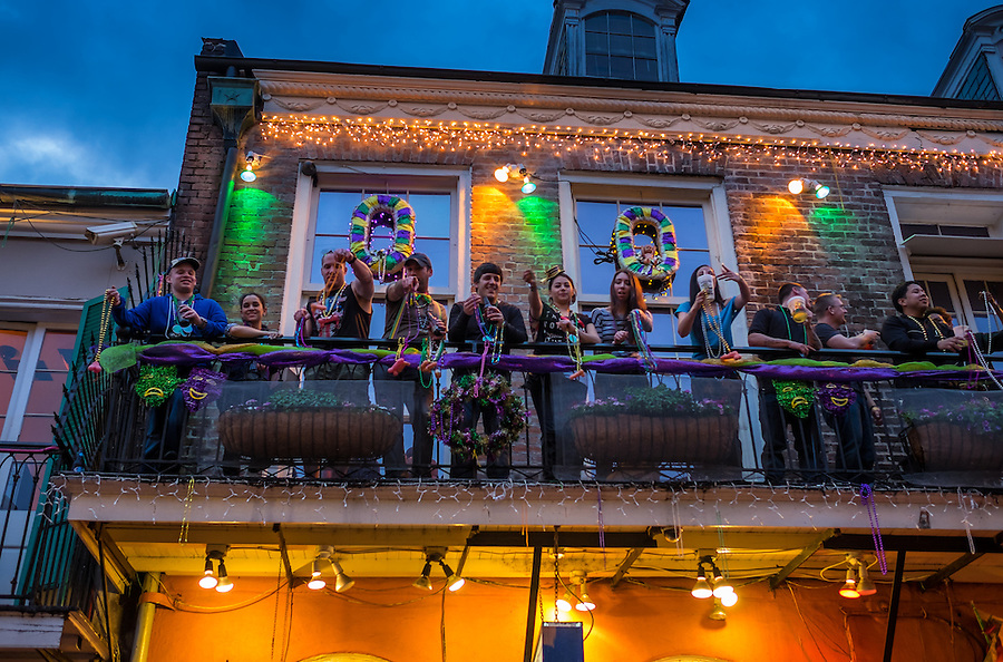 NEW ORLEANS - CIRCA FEBRUARY 2014: People showing Mardi Gras beads in balcony over Bourbon Street in the New Orleans French Quarter in Louisiana, at night.