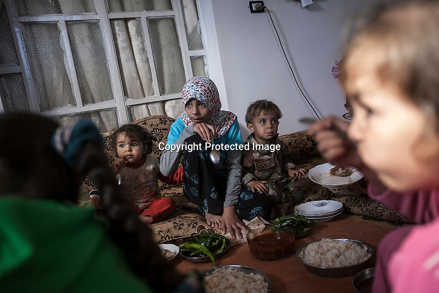 In this Thursday, Oct. 03, 2013 photo, the grandsons and grandaughters of MOHAMMED AHMED KALE (not pictured), take a lunch meal at their family house in Kafr Lata, a ghost village in a top of a mountain subdued under heavy shelling and bormbardments due the fighting between opposition fighters and government forces in the Idlib province countryside of Syria. Mohammed's whole family, included his six sons with their families and four daughters, is one of two families, that refuse to leave the village despite the heavy bombardments as four of his sons fight at the frontline situated one km from home. (AP Photo)