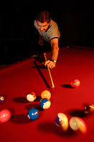 Chad Gardner shoots pool at his home in Bountiful, Utah November 10, 2005