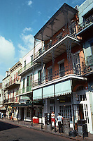 New Orleans:  Bourbon St. at Iberville.  Narrow street and sidewalk. Buildings  are commercial with residential above.