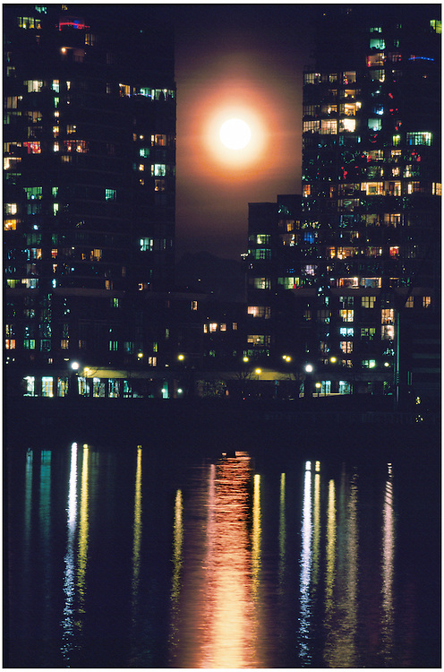 Full moon rising over buildings at Citygate, reflected in waters of False Creek, Vancouver, BC