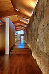 The main hallway from the front entry. Rock and wood blend together. Ross Kribbs & Michael Brands photo.