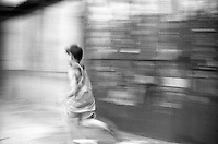 Boy running on the street. Matka, Near Skopje, Macedonia, 1999.