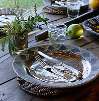 Detail of a place setting on a rustic table which has been laid for lunch outdoors