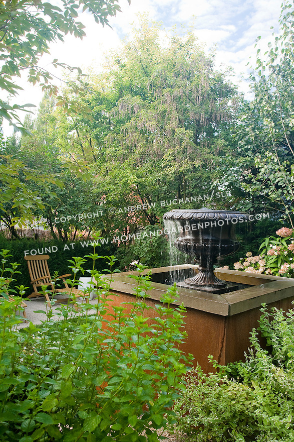 A water feature set among lush mixed beds serves as a focal point in this multi-levelled Seattle back yard.