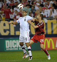 US midfielder Clint Dempsey (8) plays the ball while being pressured by Poland defender Dariusz Pietrasiak (24).  The U.S. Men's National Team tied Poland 2-2 at Soldier Field in Chicago, IL on October 9, 2010.