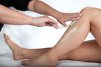 A beautician performs a wax epilation on a young women. **model release available**
