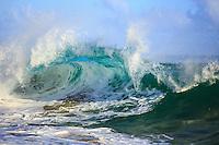 A giant wave curls into various shades of blue at Secrets Beach, Kaua'i.