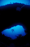 Divers under the archway on the South of Elphinstone  reef.  This archway is at a depth of greater than 50 metres. Southern Egyptian Red Sea
