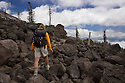 WA04447-00...WASHINGTON - Hiker on the Loowit Trail crossing boulder field on the southwest side of Mount St. Helens in Mount St. Helens National Volcanic Monument.