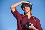 A pretty female photographer holds her camera and shields her eyese from the sunlight outdoors.