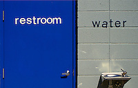 """AJ1717, restroom, water fountain, Blue door of a restroom next to a water fountain hanging on a gray wall. The words (""""""""restroom, water"""""""") are on the (door, wall)."""