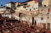 General view of Chouara tannery Fez, Morocco, pictured on February 22, 2009 in the morning. The Chouara tannery is the largest of the four ancient tanneries in the Medina of Fez where the traditional work of the tanners has remained unchanged since the 14th century. It is composed of numerous dried-earth pits where raw skins are treated, pounded, scraped and dyed. Tanners work in vats filled with various coloured liquid dyes derived from plant sources. Colours change every two weeks, poppy flower for red, mint for green, indigo for blue, chedar tree for brown and saffron for yellow. Fez, Morocco's second largest city, and one of the four imperial cities, was founded in 789 by Idris I on the banks of the River Fez. The oldest university in the world is here and the city is still the Moroccan cultural and spiritual centre. Fez has three sectors: the oldest part, the walled city of Fes-el-Bali, houses Morocco's largest medina and is a UNESCO World Heritage Site;  Fes-el-Jedid was founded in 1244 as a new capital by the Merenid dynasty, and contains the Mellah, or Jewish quarter; Ville Nouvelle was built by the French who took over most of Morocco in 1912 and transferred the capital to Rabat. Picture by Manuel Cohen.