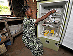 Nurse Genie Lushima retrieves supplies from a gas-powered refrigerator in a United Methodist-sponsored vaccination center in the Congolese village of Tunda.