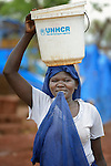 A woman carries water in the Ajuong Thok Refugee Camp in South Sudan. The camp, in northern Unity State, hosts thousands of refugees from the Nuba Mountains, located across the nearby border with Sudan. The ACT Alliance provides a variety of services in the camp.