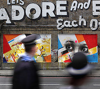 Let's Adore And Endure Each Other (detail), spray paint graffiti mural in Great Eastern Street, London, UK. A Policeman and a police woman are passing through the woman scary eyes in the painting. Picture by Manuel Cohen