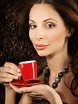 Beautiful young woman holding a red cup of espresso coffee with coffe beans background behind her