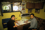 Ullapool Scotland. 1986. Bulgarian factory fishermen in cabin, reading a Finlux Design Manual, and a Kenwood Guide for Choosing Your Food Preparation Appliance.