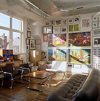 The seating area in Paul Smith's studio with a wall covered in framed artwork