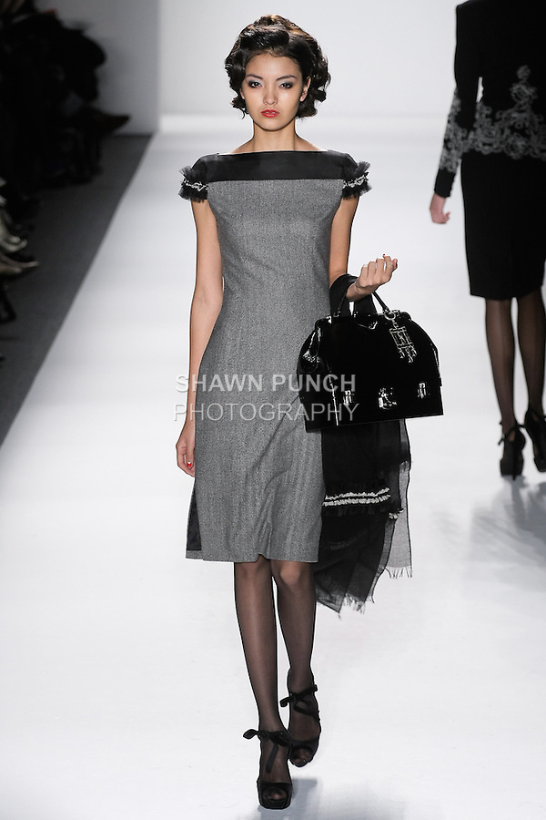 "Model walks runway in a black+ivory loro piana cashmere/wool herringbone dinner dress w/silk gazar illusion+pleated tulle fringed cap sleeves, from the Zang Toi Fall 2012 ""Glamour At Gstaad"" collection, during Mercedes-Benz Fashion Week New York Fall 2012 at Lincoln Center."