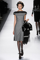 Model walks runway in a black+ivory loro piana cashmere/wool herringbone dinner dress w/silk gazar illusion+pleated tulle fringed cap sleeves, from the Zang Toi Fall 2012 &quot;Glamour At Gstaad&quot; collection, during Mercedes-Benz Fashion Week New York Fall 2012 at Lincoln Center.