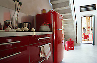 A bank of glossy red units with a thick stainless steel worktop and a retro fridge occupy one wall of the kitchen