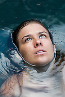 Young woman floating in water, elevated view