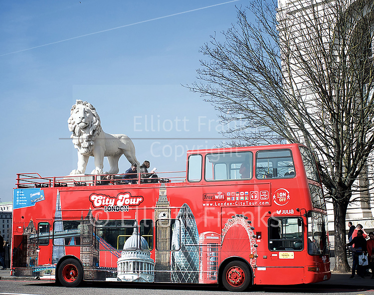Westminster Bridge <br /> an open top City Tour London bus waits at the top of Westminster Bridge with a Lion sculptor looming regally above giving the impression that the lion is on the bus! <br /> <br /> 27th March 2017 <br /> <br /> <br /> <br /> Photograph by Elliott Franks <br /> Image licensed to Elliott Franks Photography Services