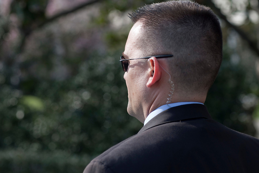 A Secret Service agent watches as President Obama walks towards the Oval Office at the White House in Washington.