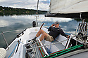 WA09113-00...WASHINGTON - Terry Donnelly sailing the waters off Vashon Island in the Puget Sound. (MR# D13)