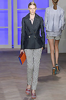 Julia Nobis walks the runway in an indigo denim double-breasted jacket, pink/white striped silk jean jacket, and navy/white striped denim slim-fit pants with ankle straps, by Tommy Hilfiger for the Tommy Hilfiger Spring 2012 Pop Prep Collection, during Mercedes-Benz Fashion Week Spring 2012.