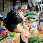 A woman tends to her vegetables at a market stall in Wonju, Korea
