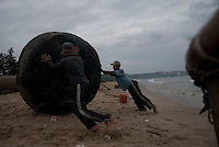 Fishermen roll their paddle boats on to shore after working all night on Mui Ne beach.