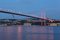 The Bosphorus Bridge at night, also called the First Bosphorus Bridge (Bogazici Koprusu), Bosphorus Strait, Istanbul, Marmara, Turkey. This bridge is one of 2 suspension bridges spanning the Bosphorus Strait, connecting Europe and Asia. It is located between Ortakoy (on the European side) and Beylerbeyi (on the Asian side). It is a gravity anchored suspension bridge with steel towers and inclined hangers. It is 1560m long with a deck width of 33.40m. The distance between the towers is 1074m and the total height of the towers is 165m. The Bosphorus Bridge had the 4th longest suspension bridge span in the world when it was completed in 1973, and is at present the 21st longest. Picture by Manuel Cohen