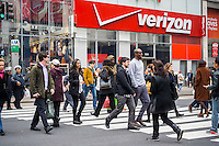 Pedestrians cross Herald Square in front of a Verizon Wireless store in New York on Friday, March 18, 2016.  (© Richard B. Levine)