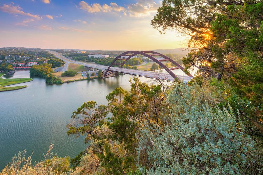 Rays of light sneak through the trees near the 360 Bridge outside of Austin, Texas.