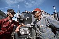 Texas, 1978. At the Truck Stop. Two drivers exchanging highway news in front of their trucks, the CB antenna is very visible. CB radio is esential on Texas Highways.
