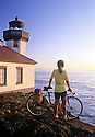 CC03048-60...WASHINGTON - Cyclist at Lime Kiln Light at Lime Kiln State Park on San Juan Island. (MR# S1)