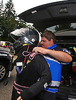 Aug. 2, 2014; Kent, WA, USA; NHRA funny car driver Terry Haddock (right) helps dress wife, top fuel dragster driver Jenna Haddock into her safety gear during qualifying for the Northwest Nationals at Pacific Raceways. Mandatory Credit: Mark J. Rebilas-