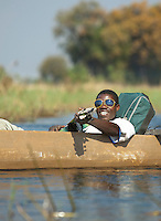 People living in the Okavango Delta often travel by Makoro, a dug out wooden canoe. Near Seronga, Botswana. The Polers Trust is a community initiative offering tours to tourists.