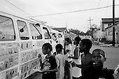 New Orleans, Louisiana.USA.July 28, 2006..Children in the 7th ward eat ice cream in the streets that now have a fraction of the population returning to live. This region was heavily damaged one year earlier hurricane Katrina hit and the levees broke leaving 80% of the city flooded. Within hours of this photo a quadruple homicide took place a few blocks from this street....